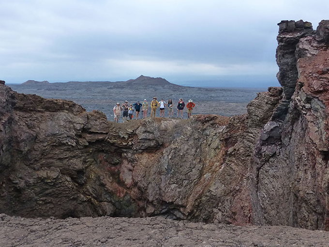 UC Davis geology undergraduates in an introductory volcanology class held each summer in Hawaii stand on the rim of a collapsed cone on Kilauea volcano with the Pu'ukoa'e spatter cone in the distance. (Rob Zierenberg/UC Davis)