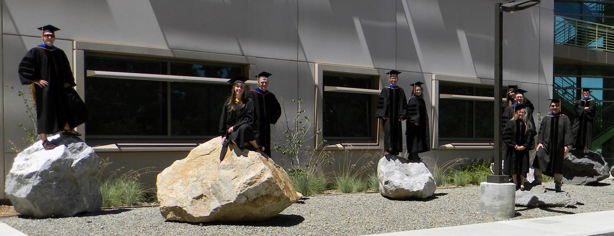 Grad students standing on rocks